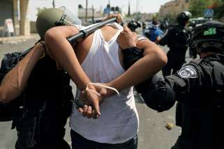Israeli security forces arrest a Palestinian man following clashes outside Jerusalem's Old City July 21.