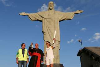 Cardinal Orani Tempesta of Rio de Janeiro holds the Olympic flame Aug. 5 as Rio Mayor Eduardo Paes and former Brazilian volleyball player Isabel Barroso look on in front of the Christ the Redeemer statue.