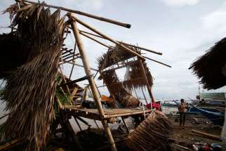 A Filipino July 17 stands next to his house destroyed by Typhoon Rammasun, locally named Glenda, in a coastal village in Batangas, south of Manila. Catholic Relief Services teams were fanning out to affected areas after Typhoon Rammasun propelled its way across the northern half of the Philippines, leaving at least 40 people dead and destroying more than 26,000 houses.