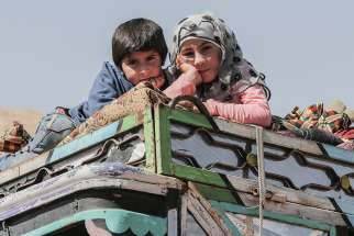 Young Syrian refugees are seen atop a vehicle at a camp in June in the village of Arsal, Lebanon.