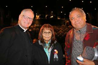 "Father Larry Lynn smiles next to residential school survivor Monique Sabourin and Steven Point, former lieutenant governor of British Columbia, after the world premiere of Father Lynn's documentary, ""In the Spirit of Reconciliation,"" in Vancouver Dec. 6."