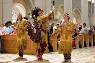 Members of the Huron-Wendat Nation perform a purification ritual at the Basilica of Sainte Anne-de-Beaupre in Quebec June 26.