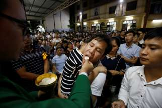 A priest distributes Communion during Mass Aug. 27 at a church in Hanoi, Vietnam.