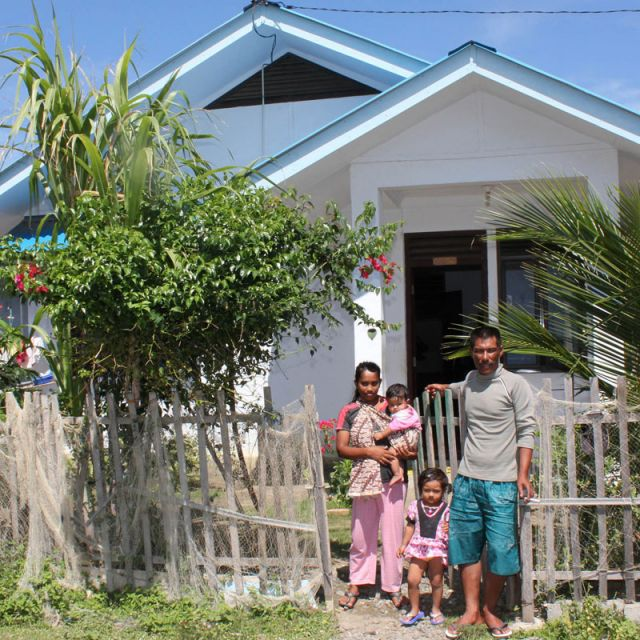 Hussein Swaid poses with his wife, Nurhiati Ibrahim, and their two young children in front of their house built by Catholic Relief Services at the fishing hamlet of Alua Naga near the city of Banda Aceh, Indonesia, Sept. 13. Seventy-five percent of Alua Naga's 3,000 inhabitants were swallowed up by the monstrous 2004 tsunami.