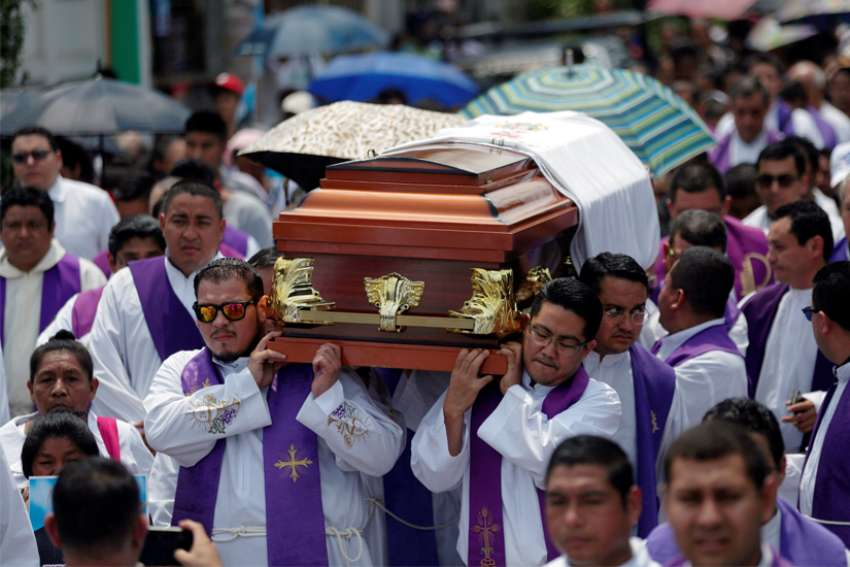 "Priests carry the casket of Father Cecilio Perez Cruz during his funeral procession in Sonzacate, El Salvador, May 20, 2019. Parishioners found Father Perez dead in his residence in Juayua early May 18 with a note nearby that said he had not paid ""rent,"" a euphemism for extortion money."