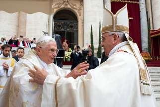 Retired Pope Benedict XVI embraces Pope Francis before the canonization Mass for Sts. John XXIII and John Paul II in St. Peter's Square at the Vatican April 27.