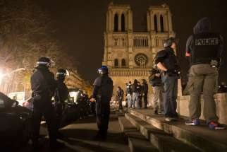 Armed police officers go on foot patrol around Notre Dame Cathedral in Paris Nov. 14. Dozens of people were killed in a series of attacks in Paris Nov. 13.
