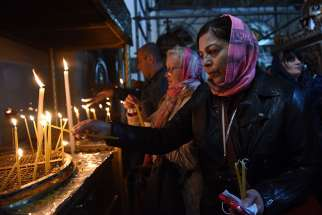 A pilgrim lights a candle Dec. 17 in the grotto of the Church of Nativity in Bethlehem, West Bank.