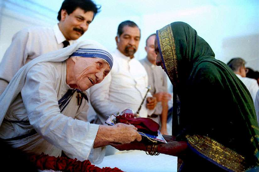 Blessed Teresa of Kolkata, India, presents documents for a new house to a villager in 1994 in Mumbai, formerly Bombay. Mother Teresa will be canonized by Pope Francis Sept. 4 at the Vatican.