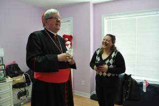 Toronto's Cardinal Thomas Collins shares a laugh with Eman Jajoo Shakar as she gives him a tour of her new house. The Shakar family, the first Iraqi refugees welcomed by the Archdiocese of Toronto in 2009, now have their own home in Brampton, Ont.