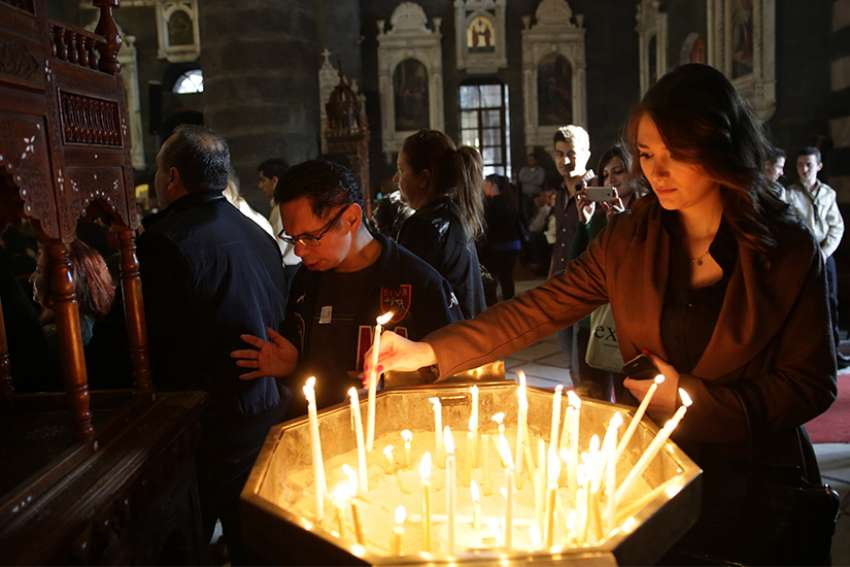 A woman lights a candle on Good Friday in 2015 in Damascus, Syria. Christians in the Middle East, particularly those who have been forced from their homes by violence and persecution, need the support of the Catholic Church, a Vatican official said.