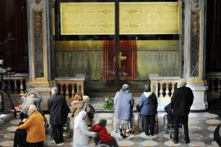 Faithful pray in front of the exposition of the Shroud of Turin in the Cathedral of Turin, Italy, March 30 2013. Pope Francis will visit Turin to venerate the shroud June 21-22.
