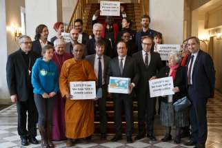 French President Francois Hollande holds a box containing an international petition to support the climate talks as he poses with religious leaders Dec. 10 at the Elysee Palace in Paris. Nearly 2 million people of faith have petitioned for a fair climate change agreement that would stop global warming and protect the poor, reported religious groups in Paris for the U.N. climate change conference.