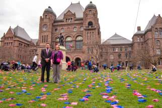 We Need A Law campaign director Mike Schouten and media relations assistant Niki Pennings on the lawn of Queen's Park, where the campaign arranged a display of 100,000 pink and blue flags to represent abortions performed in Canada each year.