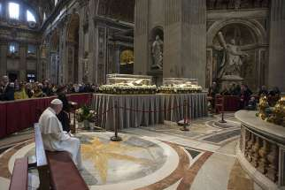 Pope Francis prays in front of the coffins containing the exhumed bodies of Sts. Padre Pio and Leopold Mandic displayed in St. Peter's Basilica at the Vatican Feb. 6. The bodies were brought to Rome at the request of Pope Francis for the Year of Mercy.