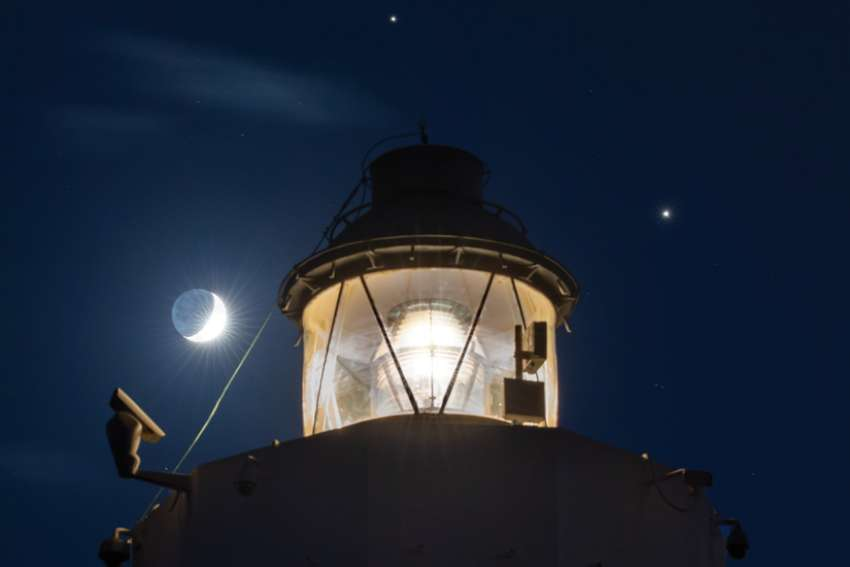 "Saturn is seen shining above the Cape Murro di Porco Lighthouse in Syracuse, Sicily, and Jupiter is seen shining to the right, in this photo taken in November. The two largest planets in the solar system will pass so close together Dec. 21 it has given rise to talk about the ""Christmas Star."""