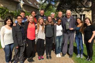 A Jean Vanier Catholic Secondary School delegation poses with the school's namesake in front of the L'Arche centre.