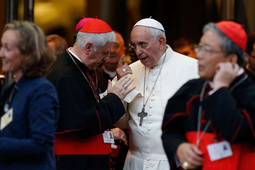 Pope Francis talks with Cardinal Giuseppe Versaldi following the concluding session of the extraordinary Synod of Bishops on the family at the Vatican in this Oct. 18, 2014, file photo.
