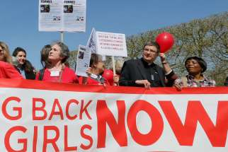"A clergyman joins others in a ""Bring Back Our Girls"" gathering in Paris April 14. A year after more than 200 Nigerian schoolgirls were kidnapped, Lagos Cardinal Anthony Olubunmi Okogie said he believed that ""God will answer our prayers"" for their return."