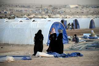 Displaced Iraqi women wait for their tent to be built June 21 at a refugee camp in Fallujah. Vatican observer to U.N. agencies in Geneva, Archbishop Ivan Jurkovic, says the world has a duty to protect refugees.