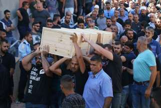 Men carry the casket of Israeli policeman Hail Sethawi July 14 who was killed in an attack at the Temple Mount compound in the Old City of Jerusalem. The deadly attack took place in the early morning hours near the Lions' Gate in the Old City walls, next to what Muslims call the Noble Sanctuary and Jews call the Temple Mount.