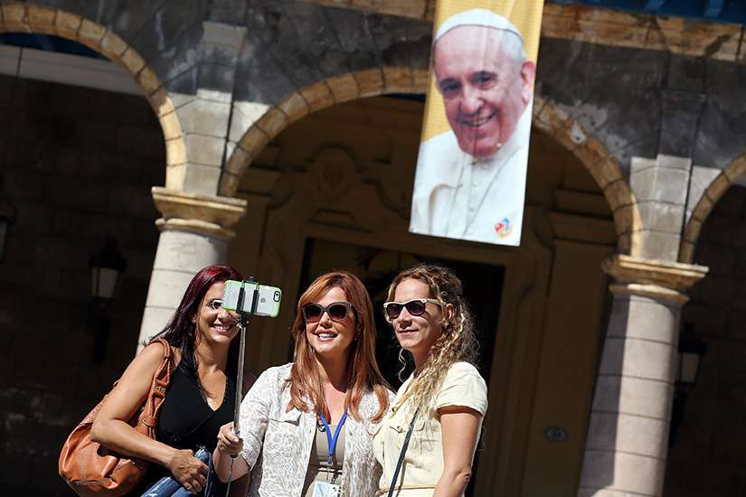 "Tourists take a ""selfie"" in front of an image of Pope Francis in Havana Sept. 18, the eve of his visit to Cuba."