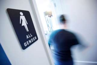 A bathroom sign welcomes both genders at the Cacao Cinnamon coffee shop in Durham, N.C., on May 3, 2016.