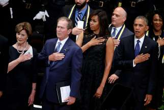 Former first lady Laura Bush, former U.S. President George W. Bush, first lady Michelle Obama and President Barack Obama hold their hands on their hearts as they sing the national anthem July 12 at a memorial service held in honor of police officers killed and wounded in shootings in Dallas.