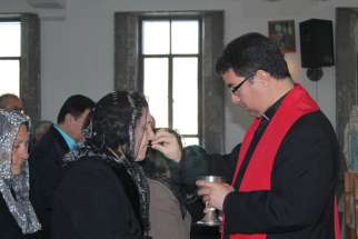 Bishop Oscar Cantu of Las Cruces, N.M., distributes Communion to displaced Iraqi Christians during a Jan. 20 visit to northern Kurdistan. Bishop Cantu traveled to northern Iraq with a delegation from the U.S. Conference of Catholic Bishops Jan. 16-20 to see the needs of displaced Christians and other religious minorities.