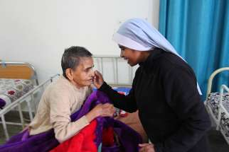 A religious sister is seen comforting a sick woman in 2016 at Snehadam Old Age Home in Gurgaon, India.