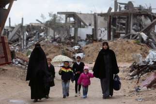 "Palestinians walk near the ruins of houses Feb. 20 that witnesses said were destroyed or damaged by Israeli shelling during a 50-day war last summer, near Gaza City. Six months after the end of the most recent war in Gaza, one aid official said there is still a ""grave humanitarian crisis."""