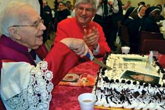 Msgr. Vincent Foy cuts the cake for his 100th birthday celebration with Cardinal Thomas Collins sharing the moment.