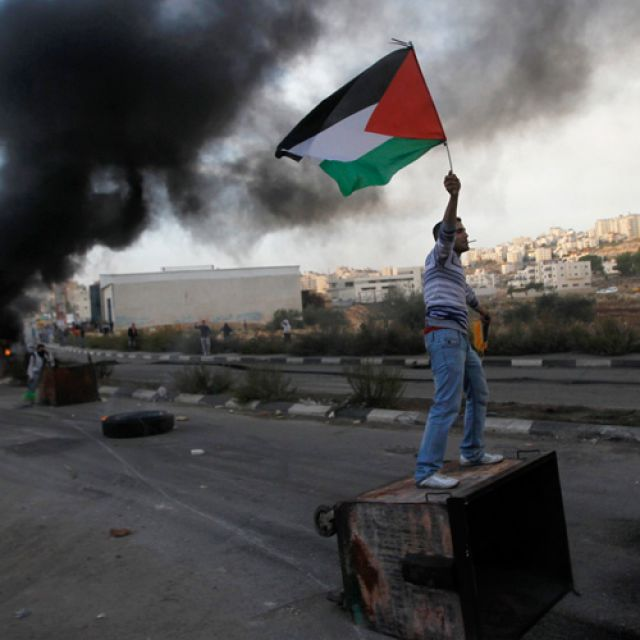 A Palestinian stone-thrower holds a flag as he stands atop a garbage bin during clashes with Israeli security forces near the West Bank city of Ramallah Nov. 18. An Israeli missile ripped through a two-story home in a residential area of Gaza City, killi ng at least 11 civilians, including four young children, in the single deadliest attack of Israel's offensive against Islamic militants.