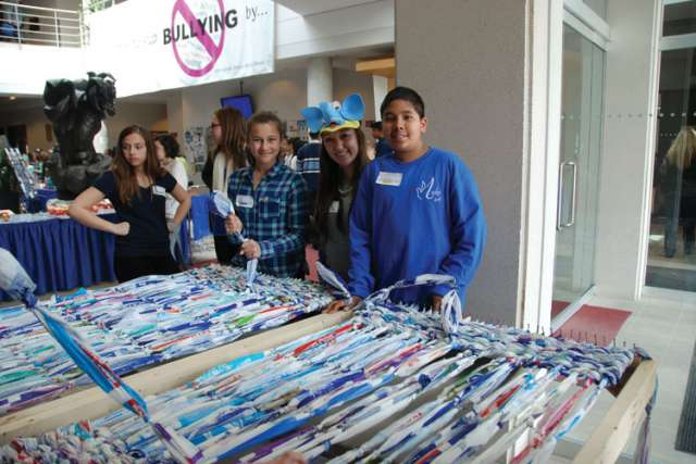 Students from the York Catholic school board weave together four-litre milk bags which are shipped to places like Haiti as protective packaging for other goods then distributed for use as sleeping mats.