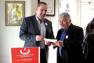 Louay Dawaf, left, receives a donation to aid Iraqi refugees at Jesus the King Melkite Church on April 12.