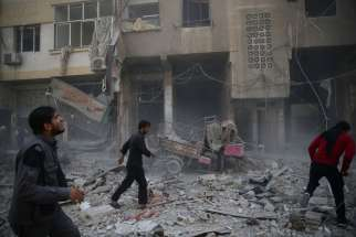 en inspect a damaged site after an Oct. 26 airstrike on the rebel-held besieged region of Douma in Damascus, Syria.