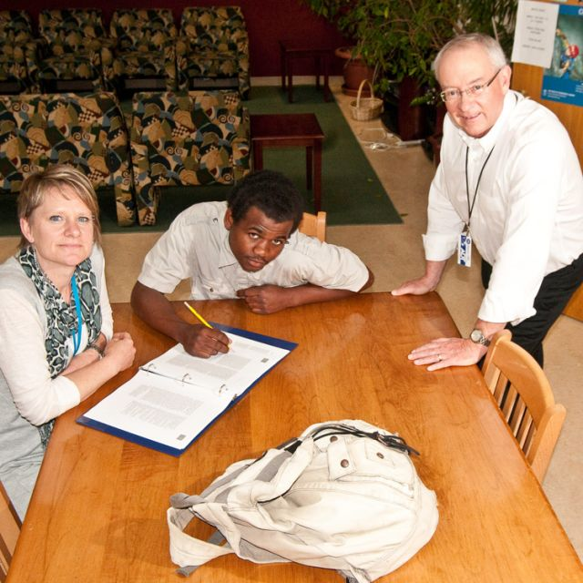 Team leader Julie Neubauer, left, and Bruce Rivers, right, sit down with Michael, a Covenant House resident.