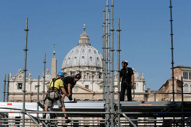 Workers erect a media platform outside St. Peter's Square at the Vatican April 22 in preparation for the April 27 canonization of Blesseds John XXIII and John Paul II.