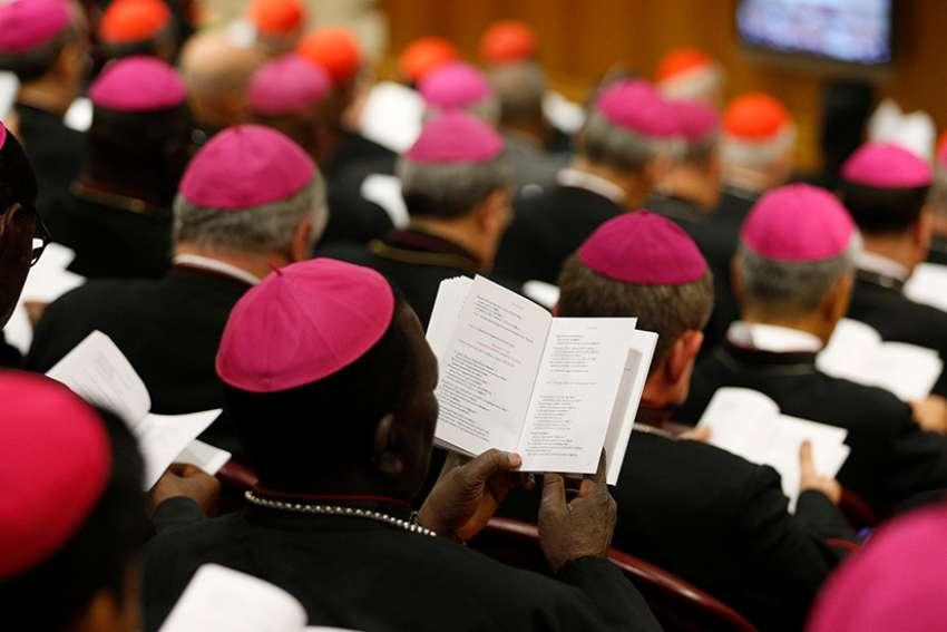 Bishops pray at the start of a session of the Synod of Bishops on young people, the faith and vocational discernment at the Vatican Oct. 9.