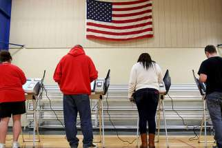 Voters cast their votes during the presidential election in Elyria, Ohio, on Nov. 8, 2016. Preliminary exit polls indicate that white Catholics, evangelical and Mormon vote voted for Trump in wide margins.