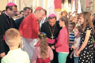 Cardinal Pietro Parolin, Vatican secretary of state, in red vestments, greets young people during a June 18 visit to Lviv, Ukraine. Although his visit included meetings with the state officials, church leaders and religious communities, Cardinal Parolin said the main purpose was to express the solidarity with people suffering from the war in the east.