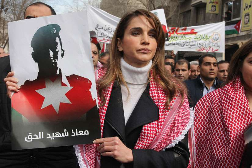 Jordan's Queen Rania holds a picture of First Lt. Muath al-Kasasbeh, executed Jordanian pilot, during a Feb. 6 march in Amman. As Jordan steps up airstrikes on Islamic State targets in Syria to avenge the murder, Catholic and other leaders are hoping tha t the tragedy can still yield good for the future.