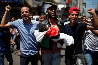 Mourners carry the body of 8-month-old Palestinian Laila al-Ghandour, who died after inhaling tear gas at the Israel-Gaza border during a May 15 protest against the U.S embassy move to Jerusalem.