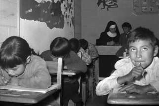 A young boy with other students and a nun in a classroom at the Pukatawagan Residential School, Manitoba, circa 1960.