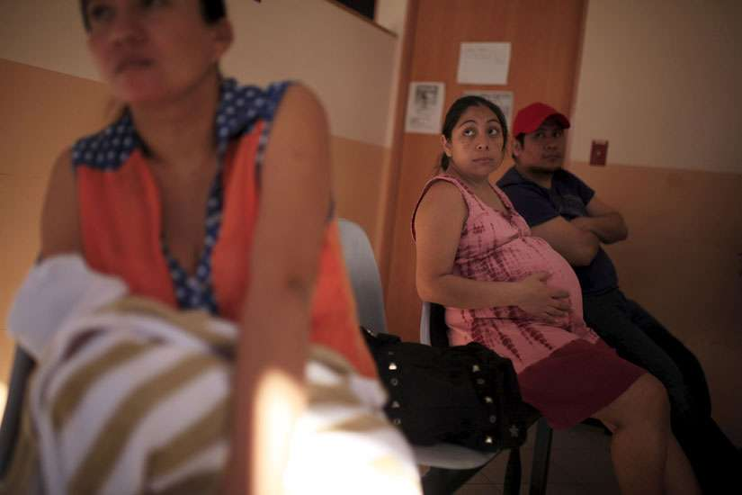 A pregnant woman waits to be seen Jan. 29 at the Women's National Hospital in San Salvador, El Salvador. Health officials have urged women to postpone their pregnancies for two years, because the Zika virus can produce microcephaly, a rare neurological condition that causes smaller heads in newborns, affecting the normal development of their brain.
