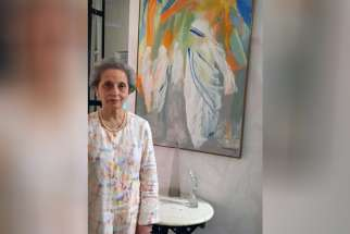 Sunita Kumar poses for a photo with her painting of Blessed Teresa March 18 at the headquarters of the Missionaries of Charity in Kolkata, India. Kumar said she once told Mother Teresa she did not paint the nun's physical features because she recognized her as a saint.