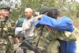 Pvt. Andry Rosales hugs a Colombian soldier after defecting from Venezuela Feb. 27, 2019. Rosales snuck out of an army base and crossed into Colombia in civilian clothes.