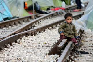 A child sits on railroad tracks near a makeshift camp for migrants in late March at the Greek-Macedonian border near the village of in Idomeni, Greece. Children are the most vulnerable and hardest hit among the world's migrants and require special protection, Pope Francis said.