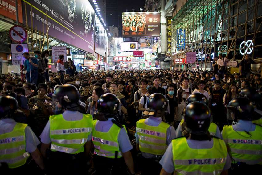 Riot police faceoff with pro-democracy protesters at Mongkok shopping district in Hong Kong Nov. 26, 2014.