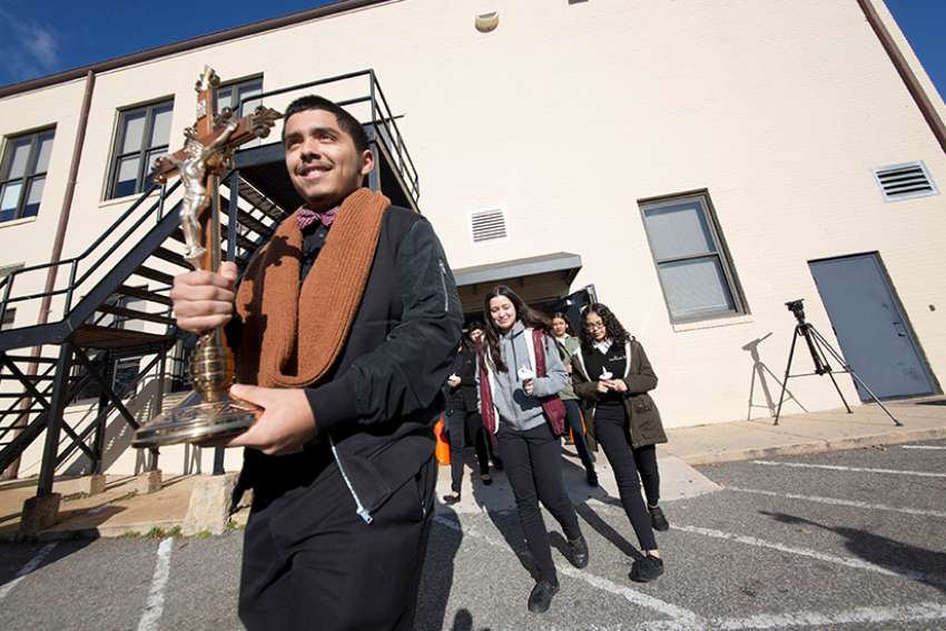 Christopher Hernandez, a senior at Don Bosco Cristo Rey High School in Takoma Park, Md., leads students as they exit the school to participate in the National School Walkout March 14. During the walkout students prayed 17 Hail Marys and released 17 balloons, one for each of the people killed in a Feb. 14 school shooting in Parkland, Fla.